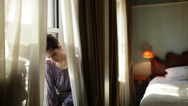 Loving young couple sitting on windowsill