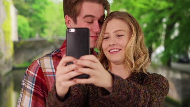 vidéos et rushes de loving young couple taking picture for social media with mobile phone - belgique