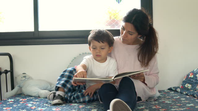 loving young mother reading a bedtime story to her son both sitting on bed having fun - toddler stock videos & royalty-free footage