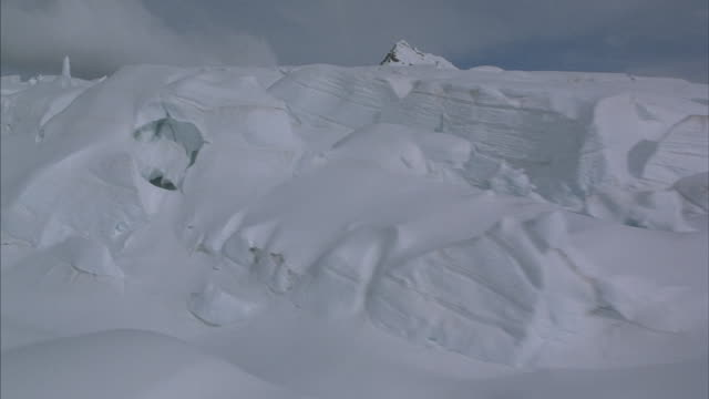 Low aerial across a beautiful snow covered glacial landscape.