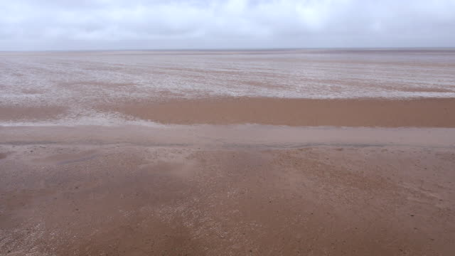 low aerial across heacham beach at low tide - low tide stock videos & royalty-free footage