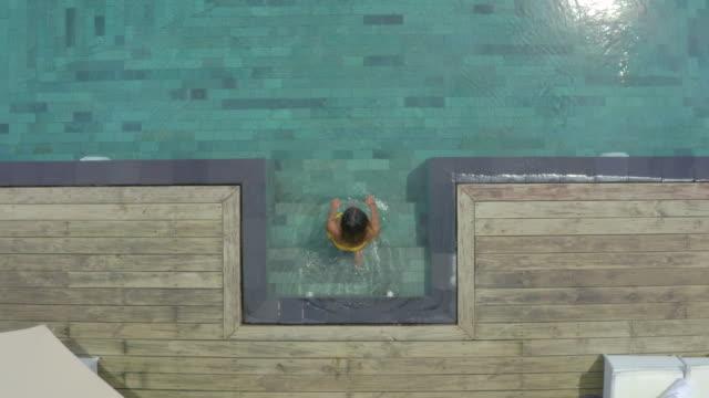 stockvideo's en b-roll-footage met low aerial: beautiful young woman in bikini entering swimming pool - buitenbad