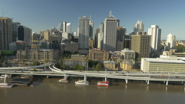 low aerial drone looking north east over river - brisbane city skyline, including brisbane river, pacific motorway, heritage building, treasury... - north pacific stock videos & royalty-free footage