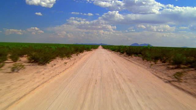 Low aerial over dirt road through arid landscape / camera rises and descends / El Paso, Texas
