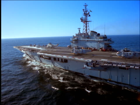 low aerial past aircraft carrier with helicopters on ocean / brazil - aircraft carrier stock videos & royalty-free footage
