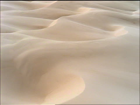 vidéos et rushes de low aerial point of view over untouched sand dunes / california - beige