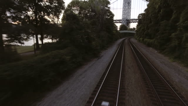 Low aerial tracking shot along train tracks in New York City