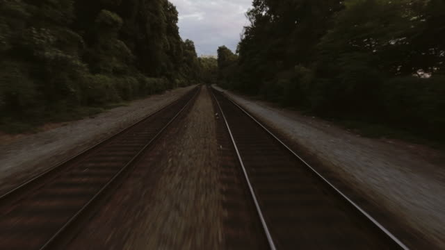 low aerial tracking shot along train tracks in new york city - zugperspektive stock-videos und b-roll-filmmaterial