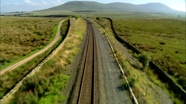 Low aerial view over railroad tracks towards Ribblehead / over Ribblehead Viaduct / North Yorkshire, England