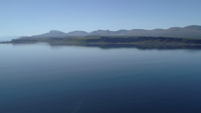 low aerial view over water, the calm blue water rippling gently towards the shores of the scottish coast - hebrides stock videos and b-roll footage