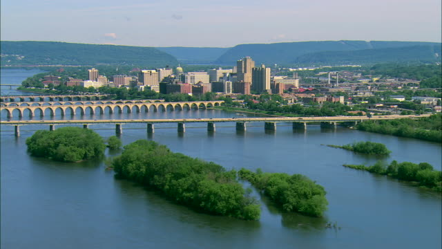 low altitude aerial approaching the john harris bridge over the susquehanna river and interstate 83 traffic with the city of harrisburg, pa behind - ペンシルベニア州点の映像素材/bロール