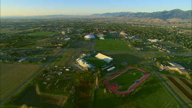 vídeos de stock, filmes e b-roll de low altitude aerial flight over campus of montana state university with town of bozeman in bg - bozeman