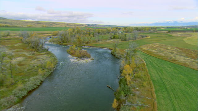 vídeos de stock, filmes e b-roll de low altitude aerial over the gallatin river in autumn near bozeman, mt - bozeman
