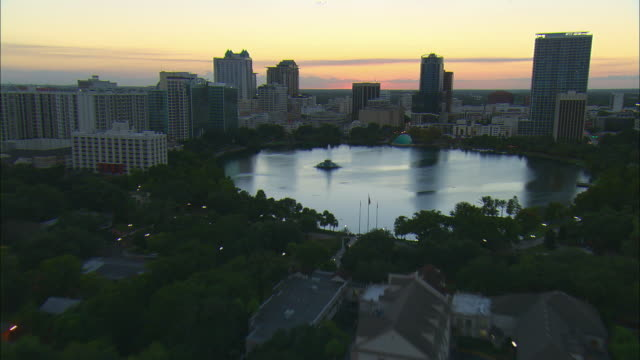 low altitude aerial pass over lake eola fountain then toward downtown orlando skyline at sunset - orlando florida stock videos & royalty-free footage