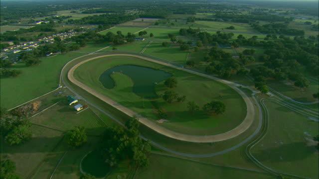 low altitude aerial pass over large equestrian facility near ocala, fl - pferdestall stock-videos und b-roll-filmmaterial