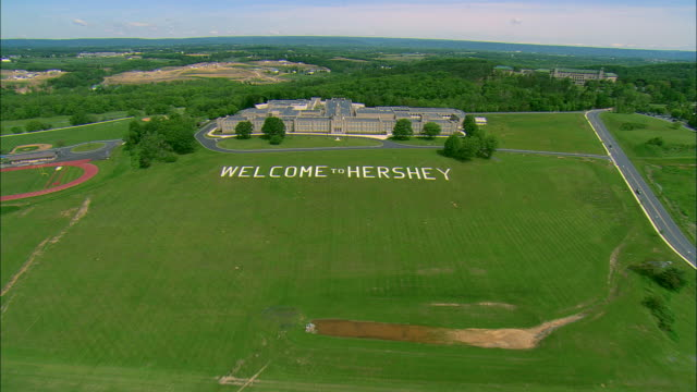 Low altitude aerial pass over the Welcome to Hershey sign on the front lawn of the Milton Hershey Middle School at Hershey, PA