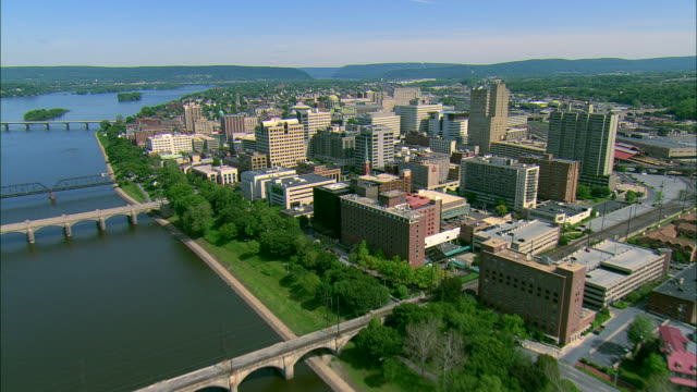 stockvideo's en b-roll-footage met low altitude aerial passing over the susquehanna river and over downtown harrisburg and the pennsylvania state capitol complex to railyard beyond - pennsylvania