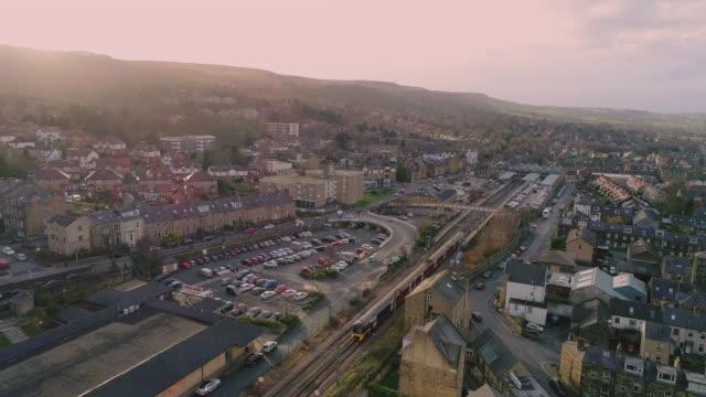 low altitude aerial video ilkley west yorkshire train arriving at dusk - スキップトン点の映像素材/bロール