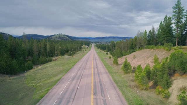 vídeos de stock e filmes b-roll de low altitude flight along the highway mt 200 near greenough, montana, in early spring. stormy weather, with the dramatic cloudy sky and heavy snowstorm at the horizon. drone video with the forward and ascending camera motion. - montana