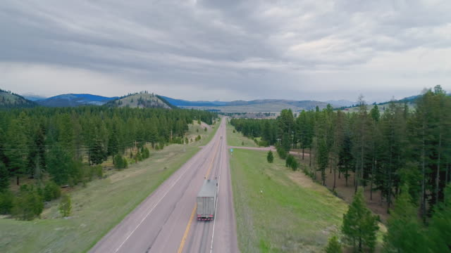 vídeos de stock e filmes b-roll de low altitude flight along the highway mt 200 near greenough, montana, in early spring. stormy weather, with the dramatic cloudy sky and heavy snowstorm at the horizon. drone video with the forward camera motion. - montana