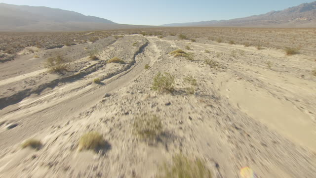 ws aerial pov low altitude flight over dry river bed and desert vegetation in death valley with tucki mountain in distance / california, united states - californian sierra nevada stock videos and b-roll footage