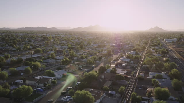 vidéos et rushes de low altitude flight over neighborhood, camera tilts up into sky - zoom out