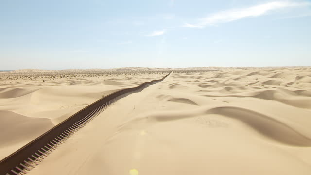 WS TU AERIAL POV Low altitude flight over sand dunes and border fence cutting across desert with Mexico left and California United States right / California, United States