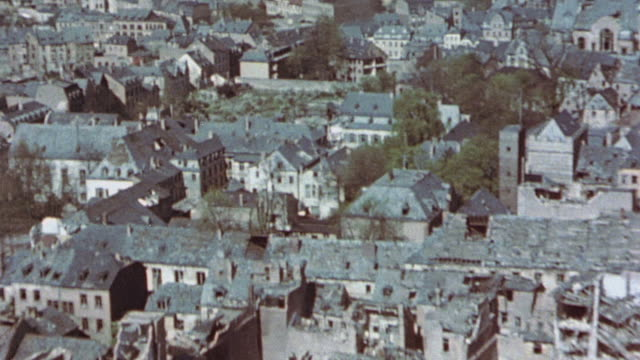 vidéos et rushes de low altitude flyover with town showing bomb damage / germany - 1945