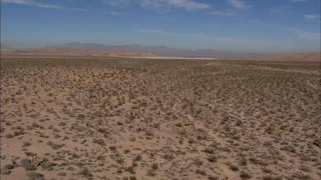 hd aerial *low altitude ws moving over desert valley scrub few dirt trails - nevada stock-videos und b-roll-filmmaterial