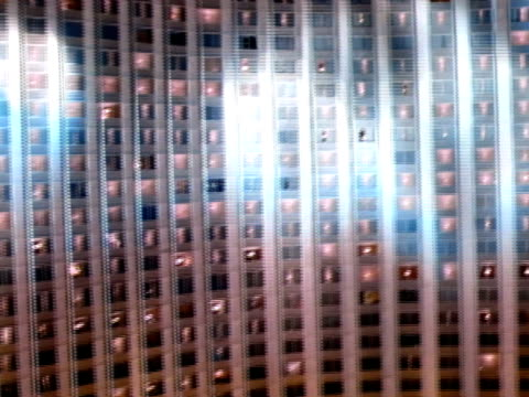 low altitude moving over parking lot dotted w/ street lights, wall of windows of hilton hotel w/ spotlights moving over building, rising past hilton... - las vegas hilton stock-videos und b-roll-filmmaterial