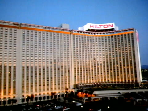 low altitude moving over parking lot toward side of hilton hotel, steep rise in altitude flying over hilton roof top sign, side of building, moving... - las vegas hilton stock-videos und b-roll-filmmaterial