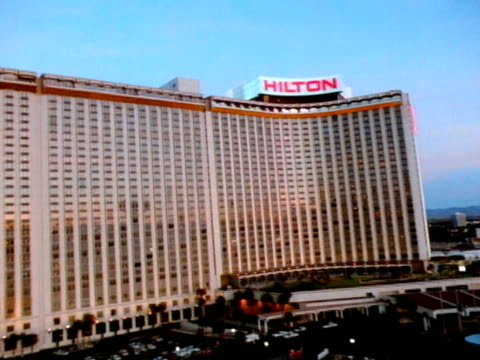 low altitude moving over parking lot toward side of hilton hotel, steep rise in altitude flying over hilton roof top sign, side of building & moving... - las vegas hilton stock-videos und b-roll-filmmaterial