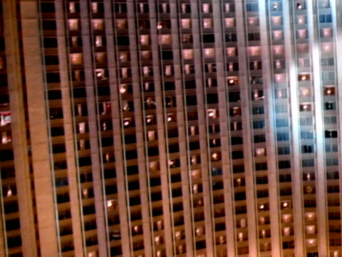 low altitude moving over parking lot toward wall of windows of hilton hotel, spotlights moving over building, steep rise up past hilton roof sign. - las vegas hilton stock videos & royalty-free footage