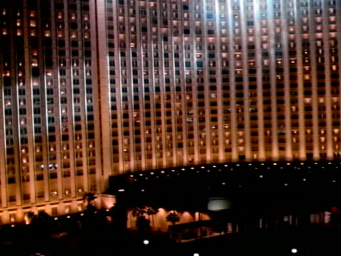 low altitude moving over parking lot toward wall of windows of hilton hotel, spotlights moving over building, steep rise up to hilton roof sign. - las vegas hilton stock-videos und b-roll-filmmaterial