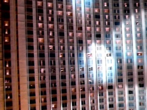 low altitude moving over parking lot toward wall of windows of hilton hotel, spotlights moving over building, steep rise up past hilton roof sign... - las vegas hilton stock-videos und b-roll-filmmaterial