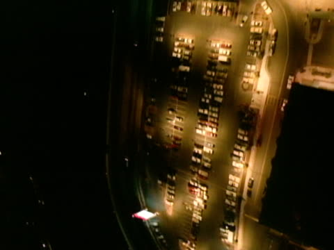 low altitude moving over parking lot toward wall of windows of hilton hotel, spotlights moving over building, steep rise up to hilton roof sign,... - las vegas hilton stock-videos und b-roll-filmmaterial