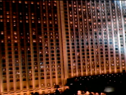 low altitude moving over parking lot toward wall of windows of hilton hotel, spotlights moving over building slo rise up past hilton roof sign. - las vegas hilton stock-videos und b-roll-filmmaterial