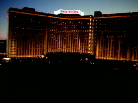 low altitude moving toward center of curved hilton hotel steep ascent up & over hilton roof sign reveals las vegas city lights beyond w/ mountains in... - las vegas hilton stock-videos und b-roll-filmmaterial
