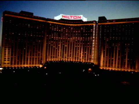 low altitude moving toward center of curved hilton hotel steep ascent up & over hilton roof sign reveals las vegas city lights beyond w/... - las vegas hilton stock-videos und b-roll-filmmaterial