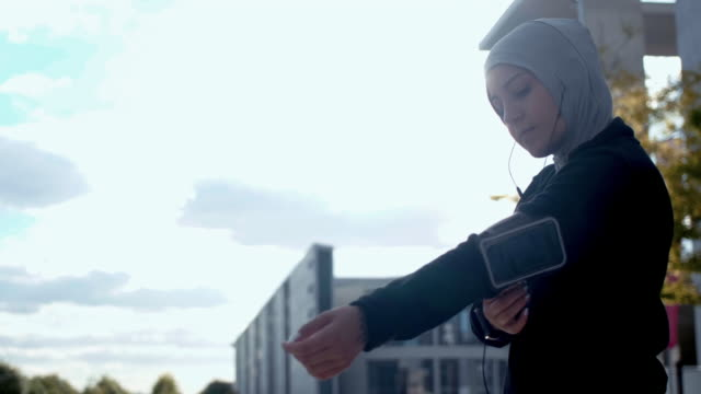 low angel view of muslim woman in sport hijab putting arm band on - arm band stock videos & royalty-free footage
