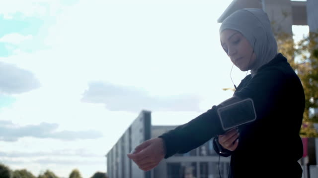 low angel view of muslim woman in sport hijab putting on arm band (slow motion) - arm band stock videos & royalty-free footage