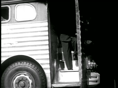 b/w low angle 1940s door of bus opening as bus driver exits looking at pocket watch - only mature men stock videos & royalty-free footage