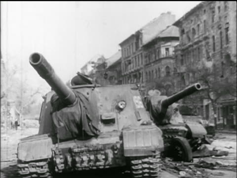 stockvideo's en b-roll-footage met b/w 1956 low angle 2 battered tanks in city street / hungarian uprising - 1956