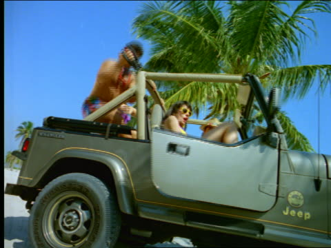 low angle 2 couples getting out of off-road vehicle on beach - ワンピース型の水着点の映像素材/bロール