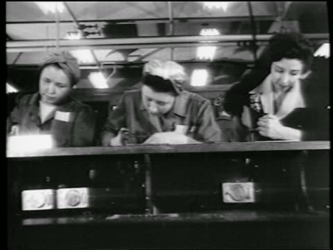 stockvideo's en b-roll-footage met b/w 1944 low angle 3 women riveting in defense plant / world war ii / industrial - first line of defense filmtitel