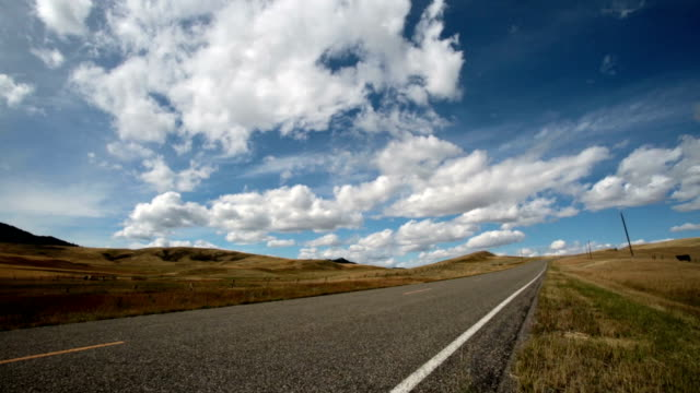 Low angle 3/4 view of highway on prairie under puffy clouded blue sky