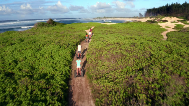 low angle aerial shot of a group of friends riding away from camera - turtle bay hawaii stock videos and b-roll footage
