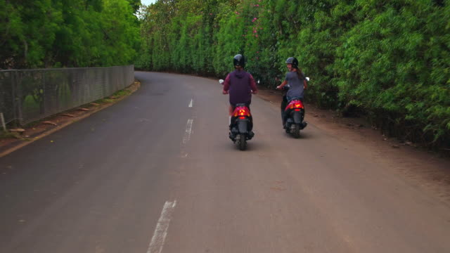 low angle aerial shot of couple riding down an empty road on mopeds - タートル湾点の映像素材/bロール