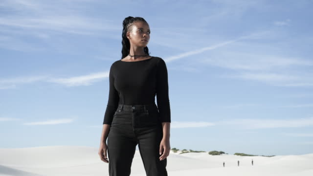 low angle, african american woman stands in desert - trousers stock videos & royalty-free footage