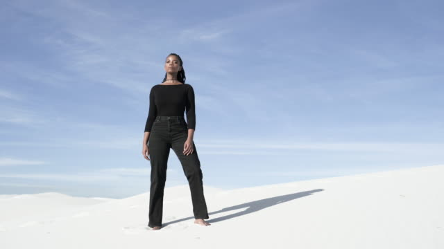 vidéos et rushes de low angle, african american woman stands in desert - endroit isolé